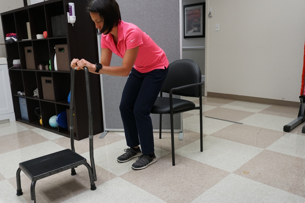standing and balancing holding to a step stool