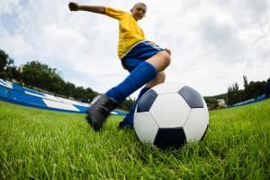 Boy soccer player hits the ball on the football field. Fish-eye lens.
