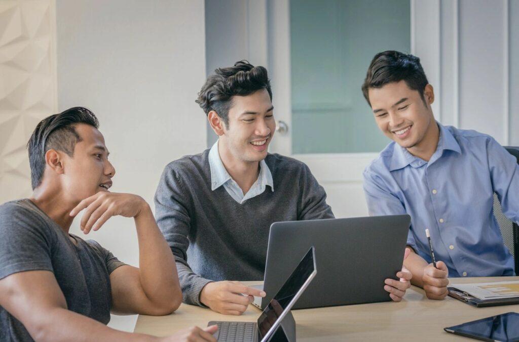 Three men looking at a laptop
