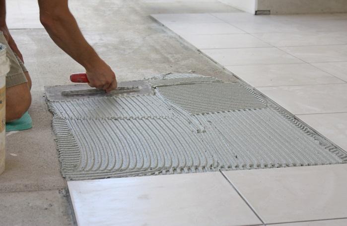 Man installing tile flooring