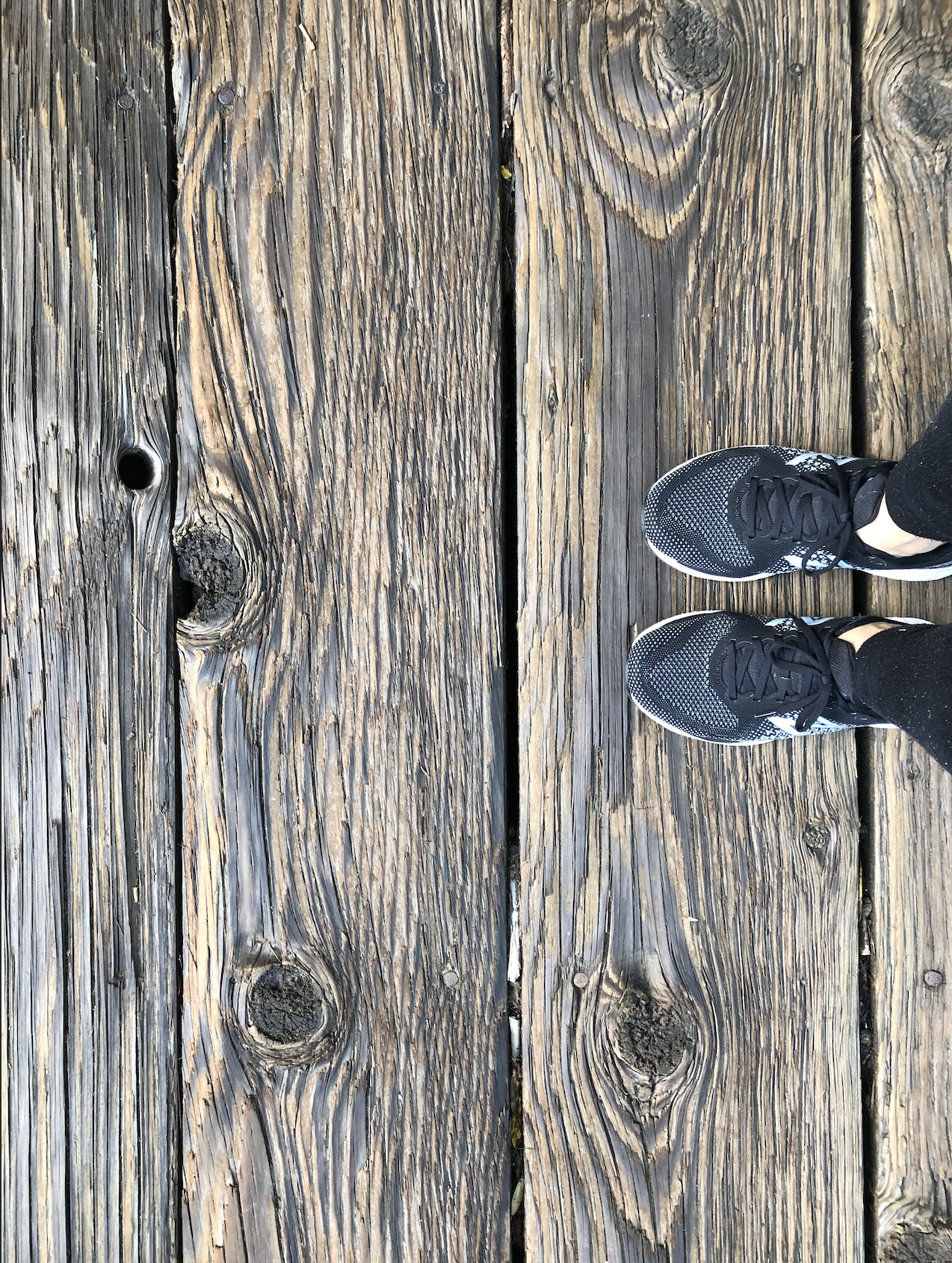 The June edition of ACT on 2021; a pair of running shoes on a wooden bridge, as a way of remembering to be human in new interactions.