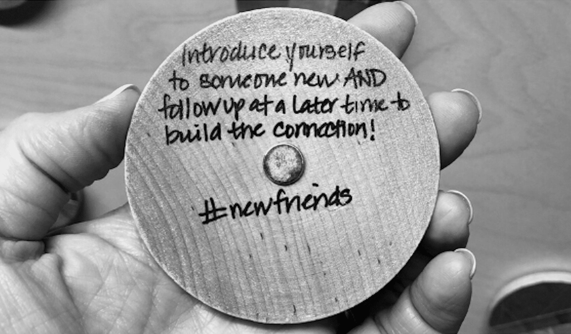 A black and white image of a disc suggesting that introducing yourself to new people, will almost always lead to new friends.