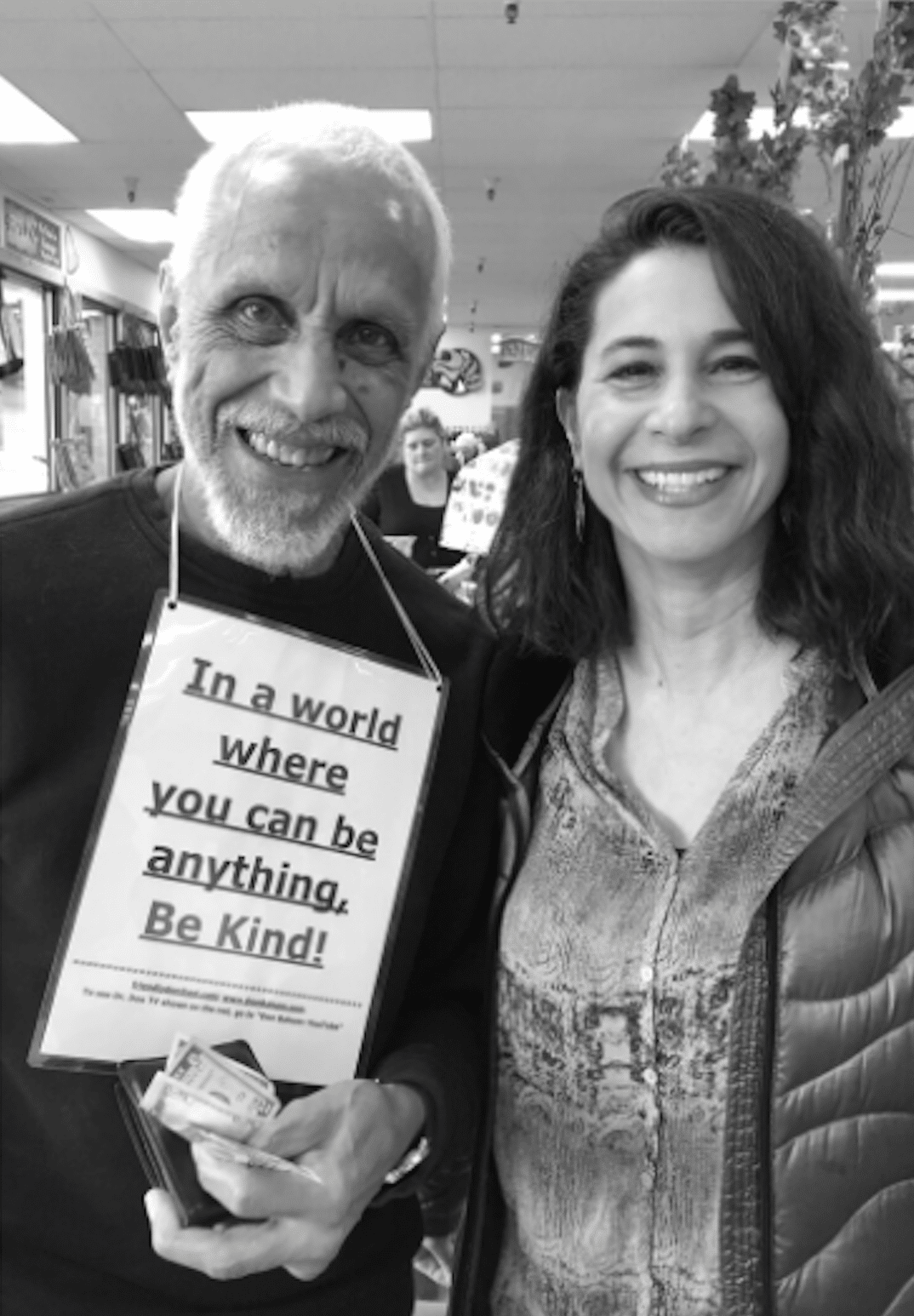 """A black and white photo of Linda Cohen and a man with a sign that reads, """"In a world where you can be anything, be kind!"""""""