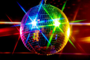 A disco ball illuminated by colorful lights.