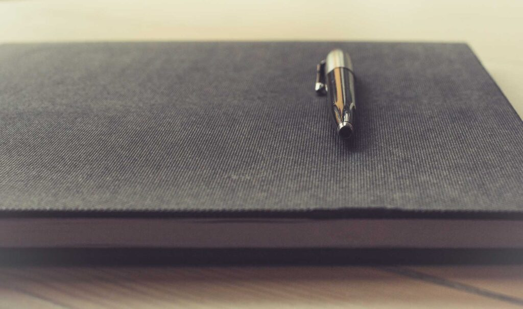 A pen resting on top of a notebook