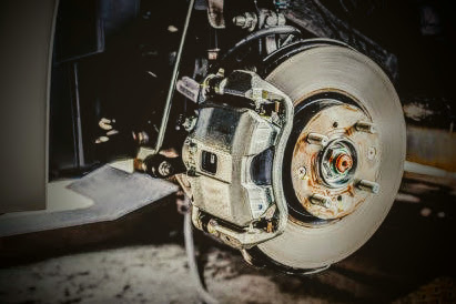 car brake pad and rotor with the wheel removed in an auto repair shop