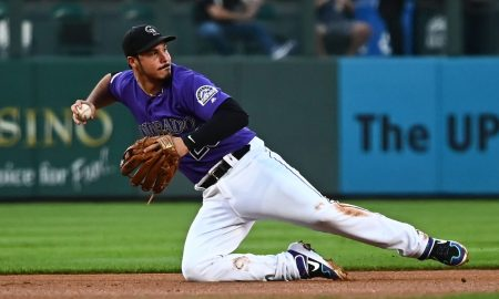 Nolan Arenado dives to his right, gets the ball, and is making a throwing motion to first or second base, wearing a purple Colorado Rockies jersey with white striped pants.