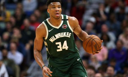 Giannis Antetokounmpo dribbling a basketball, wearing the green Milwaukee Bucks uniform in front of a crowd from 2019.
