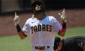 Fernando Tatis Jr. of the San Diego Padres pointing upward and celebrating a home run after crossing home plate. Umpire is in the background dusting off the plate.
