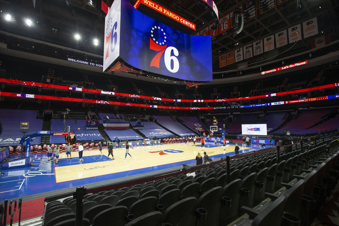 The basketball court at Wells Fargo Center with the huge scoreboard showing the 76ers logo.
