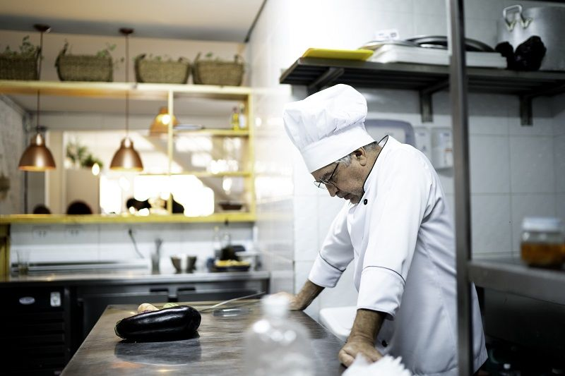 A worried senior chef in the kitchen counter cm