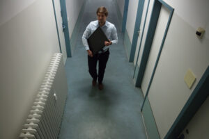 Man carrying monitor through hallway, watching through CCTV security camera