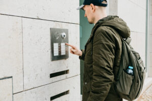 Man with bookbag using a video intercom in front of a building