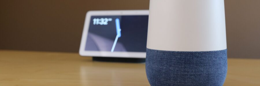 Google Home Hub sitting on desk with Google Home Max in background