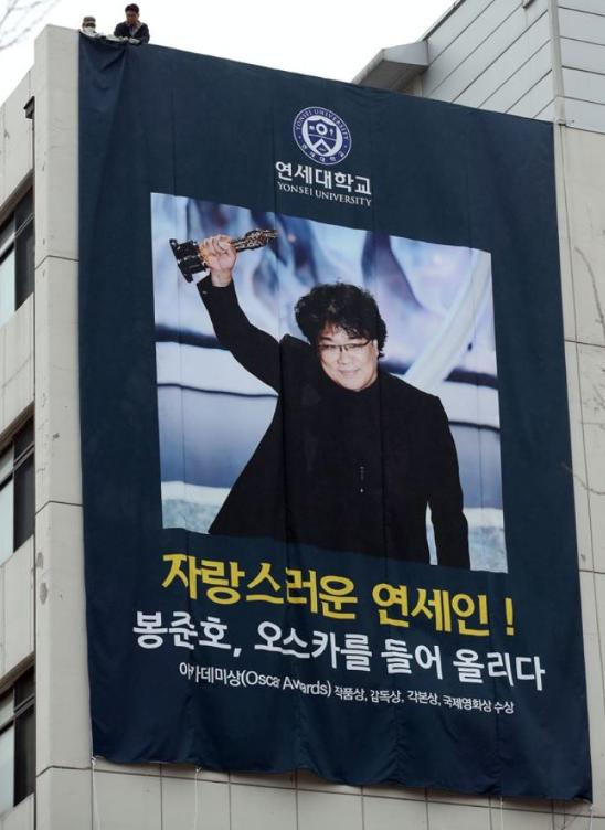 Yonsei University hangs a banner of Bong Joon Ho holding an Oscar Trophy.
