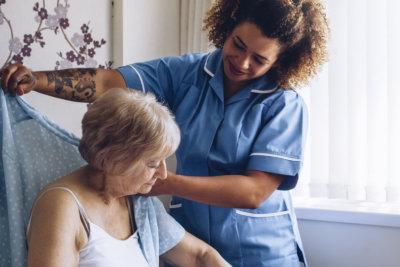 caregiver dressing senior woman