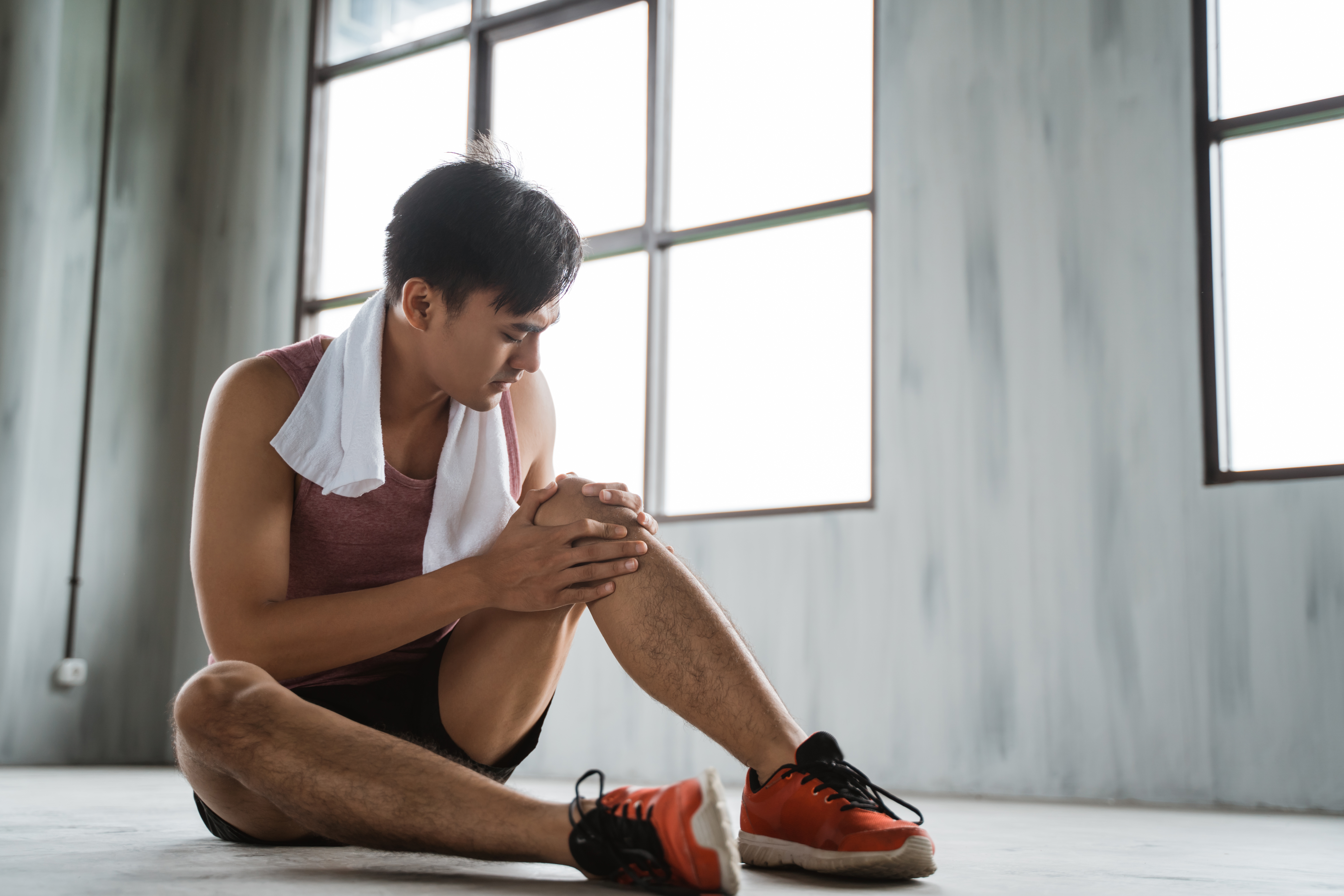 portrait of young man get knee injury while workout at the gym