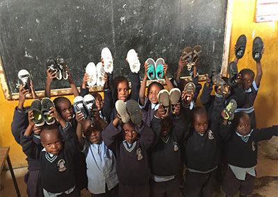 kids-showing-donation-in-front-of-blackboard