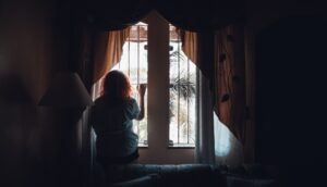 woman standing in front of a window looking outside - alone