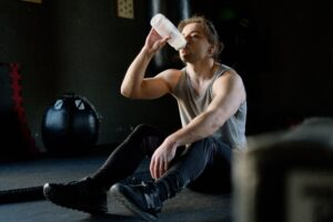 man sitting on floor drinking water trying to recover from a workout