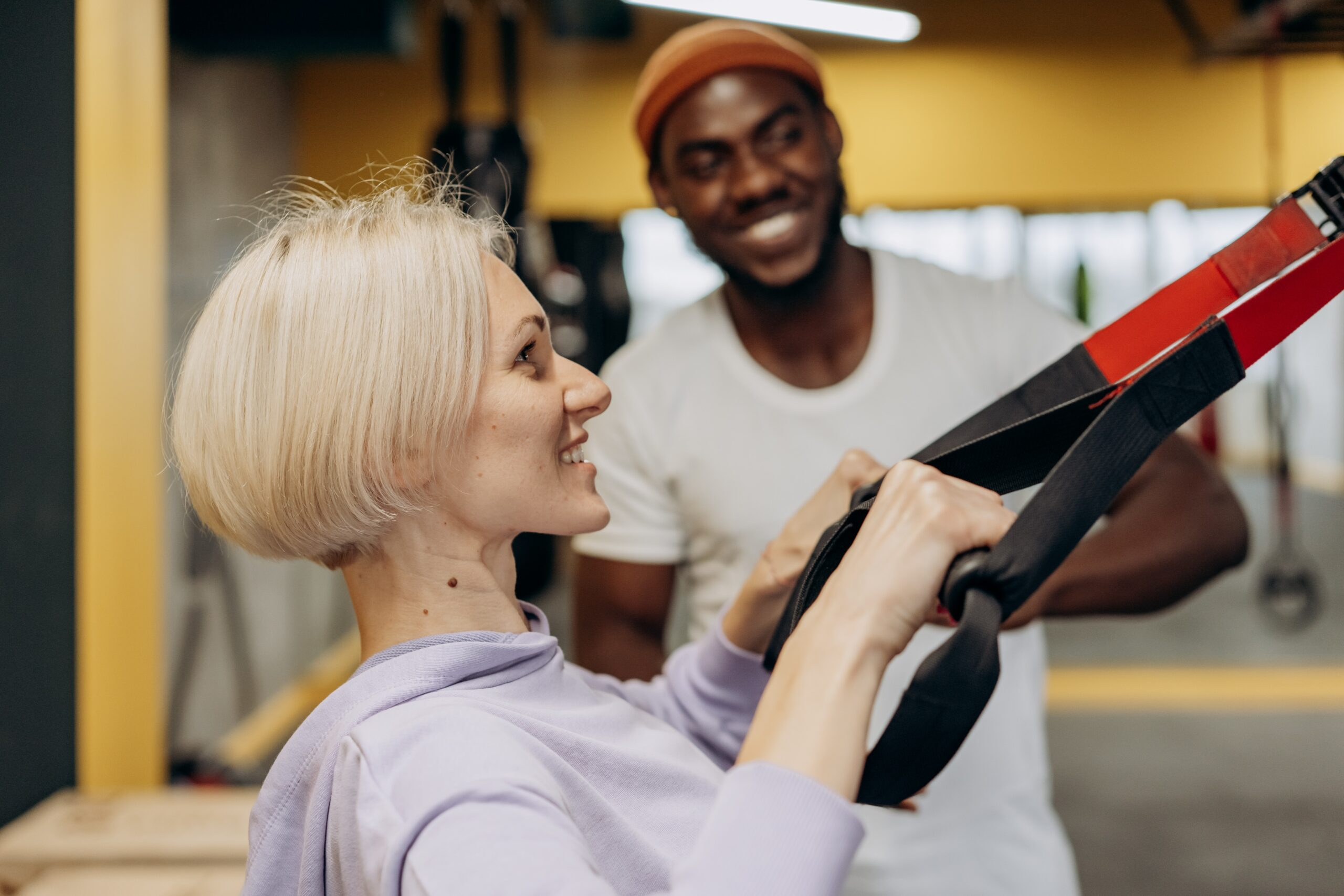 trainer helping lady exercise