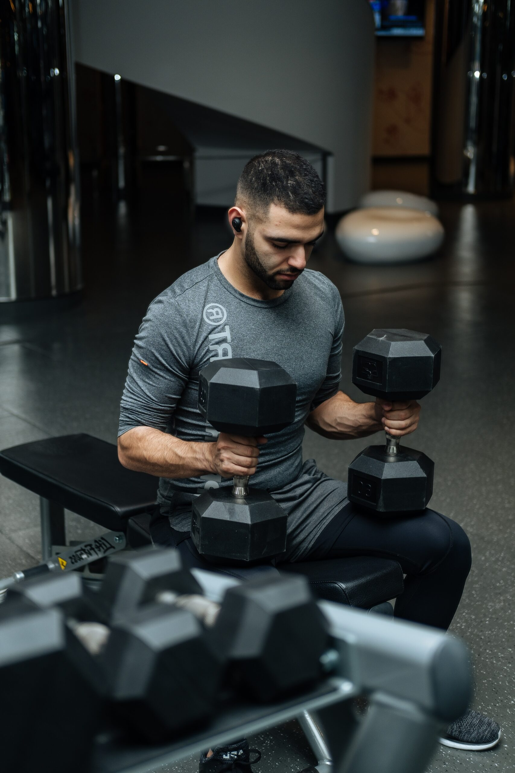 photo of man siting on bench lifting dumbells during exercise workout