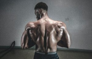 man in gym with big muscles with his back facing the camera