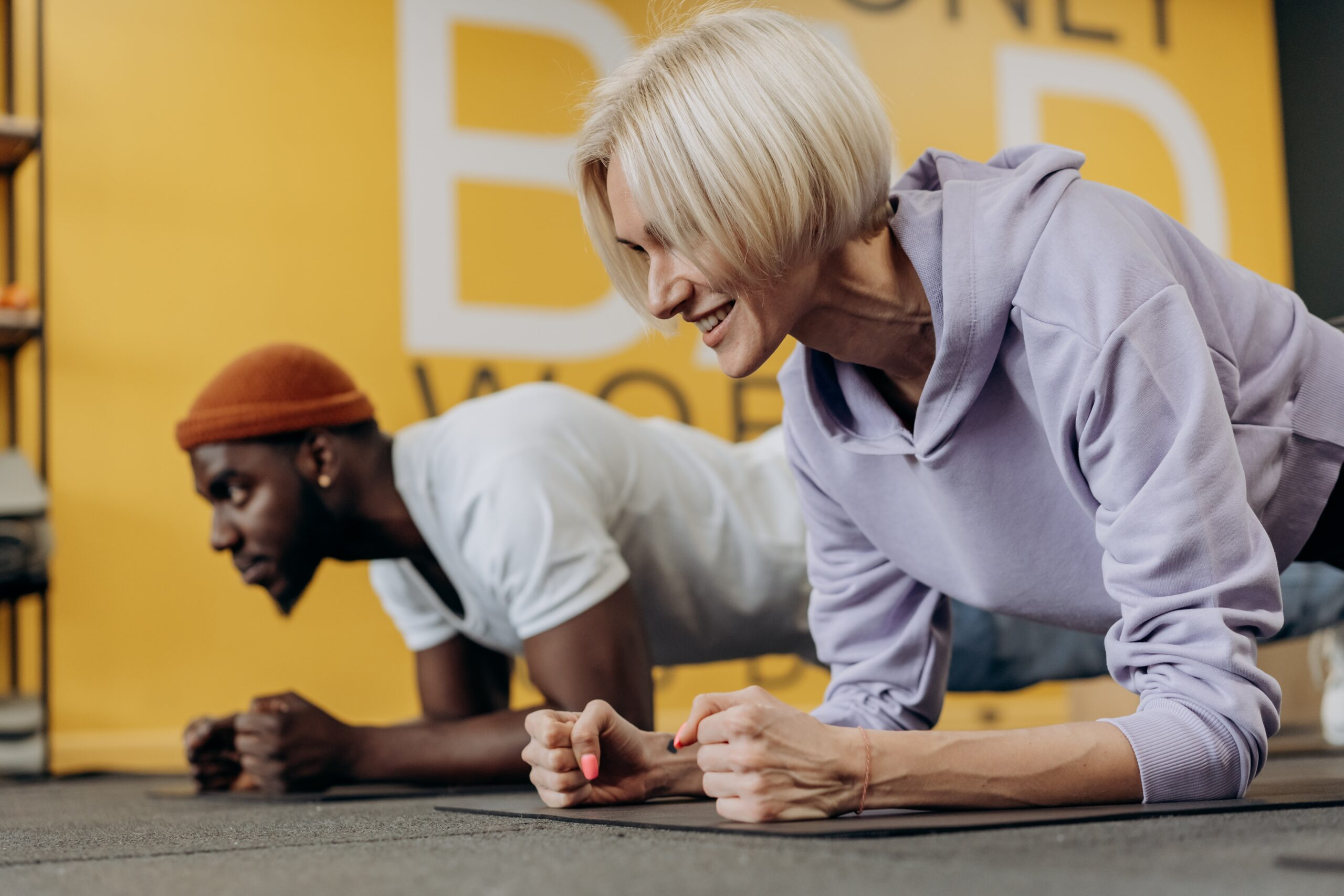 man and woman on ground doing exercise