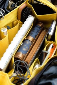 purse with different pockets containing notebook, pens, charging cable