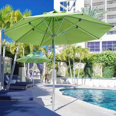 View of an open green umbrella by a pool