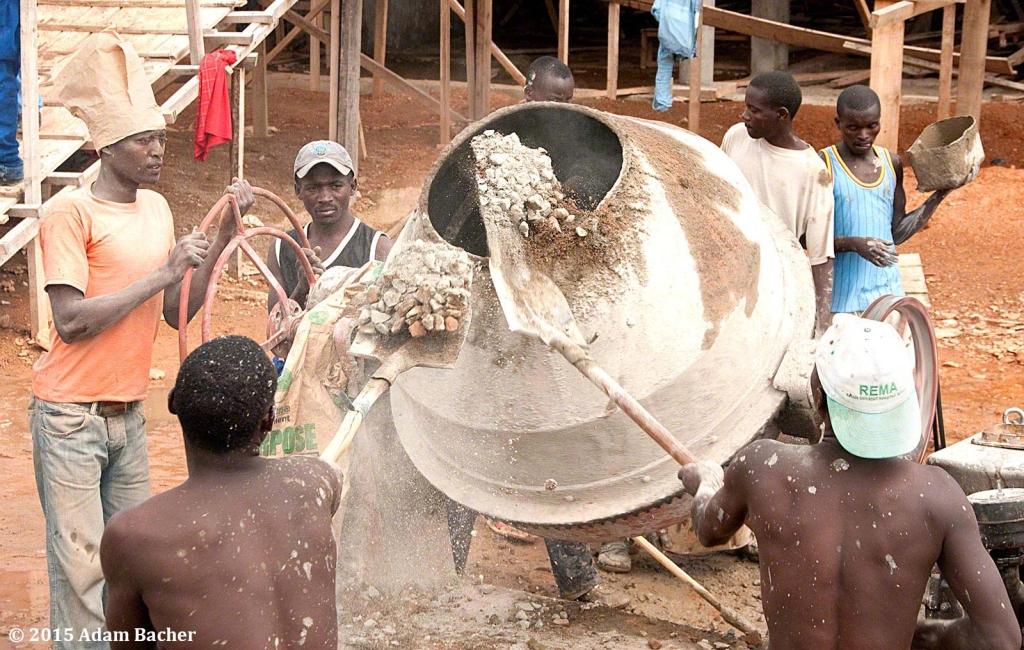portland oregon editorial photographer in rwanda -workers shoveling cement