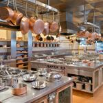 Commercial Kitchen Interior featuring silver hobs and ovens and hanging copper pots and pans.