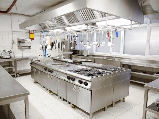 A silver metal modular unit of hobs, stoves and shelves in the middle of commercial kitchen.