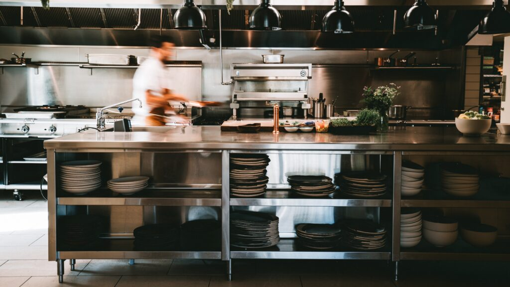 Busy open-kitchen style restaurant picturing a shelf with table ware and commercial kitchen appliances in the background.