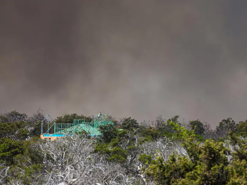 A man watches the bushfire from the roof of his partly completed home in Tranquil Drive, Esperance. Credit: The West Australian, Mogens Johansen, The West Australian