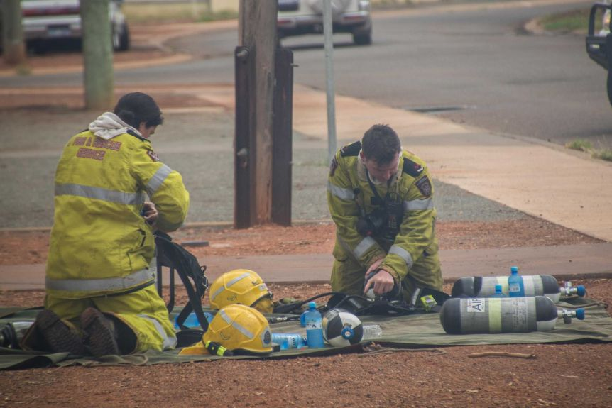 Firefighters change over oxygen tanks at a house fire in Kalgoorlie-Boulder.(ABC Goldfields-Esperance: Jarrod Lucas)