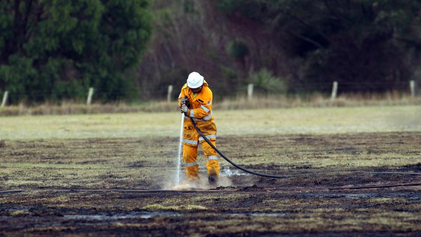 A volunteer firefighter mops up after a fire. Credit: Laurie Benson/Albany Advertiser