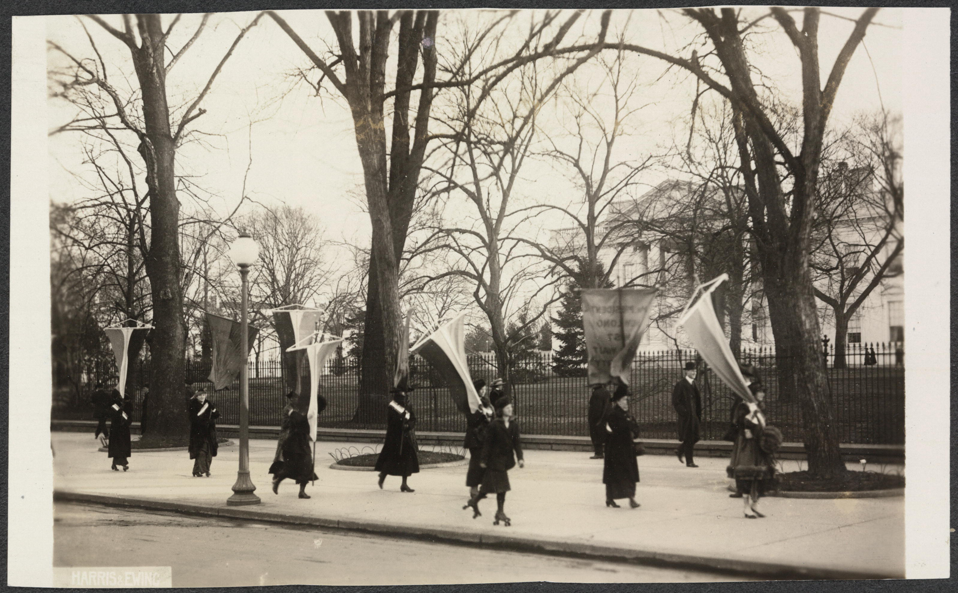 Photograph of suffragists marching in contingent with banners, picketing outside on the sidewalk in front of the White House. A woman skates by in foreground on roller skates, and a man in bowler hat strolls down sidewalk near fence.