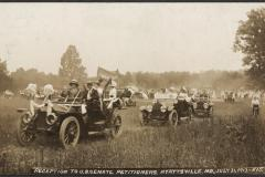 A parade of Model T type cars driving across a field