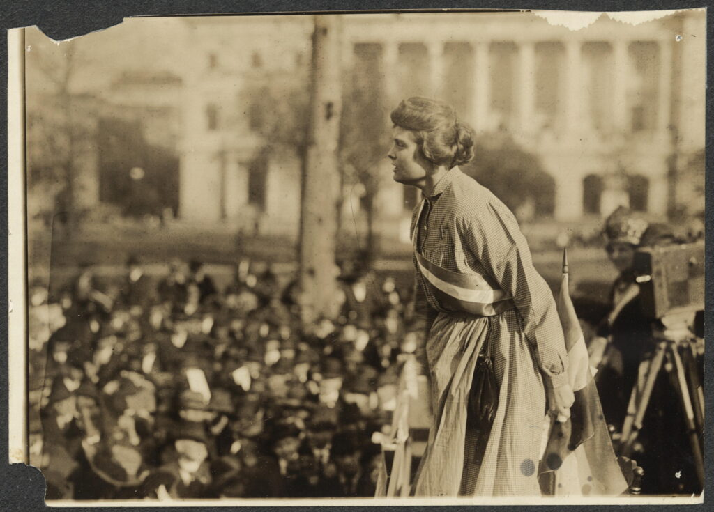 Lucy Branham dressed in replica prison garb and forcefully speaking to a crowd