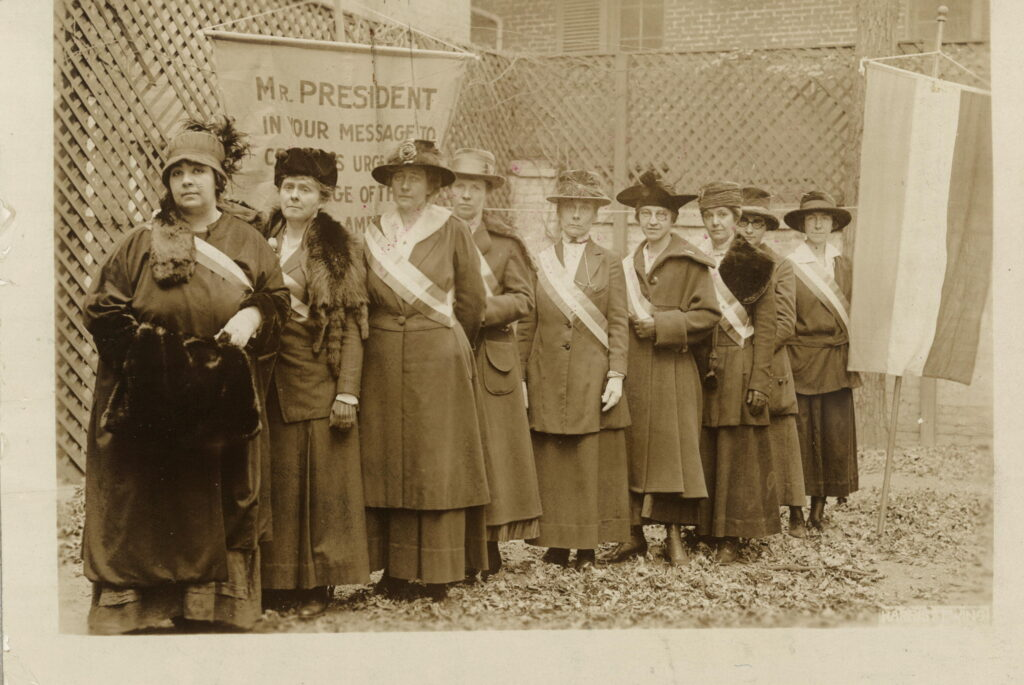 none suffragists lined up against a latticed fence with a banner addressing President Wilson.
