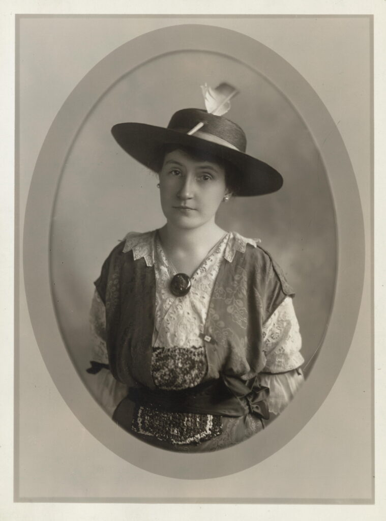 alf length portrait of Edna S. Latimer, facing camera, in hat, with brooch