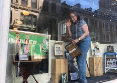 photo taken from tree of artist arranging her work in the storefront