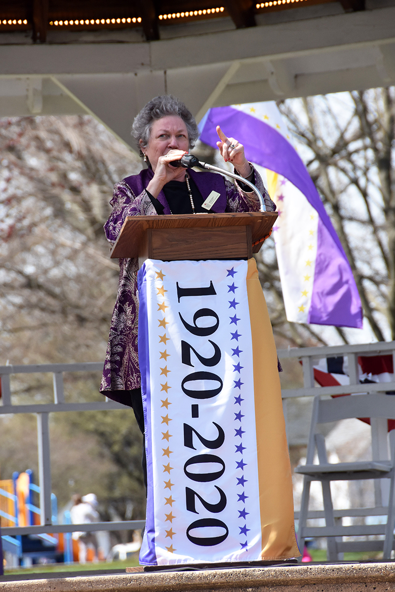 Diana Bailey at podium, Maria Darby, MWHC Board President at podium, banner says 1920- 2020