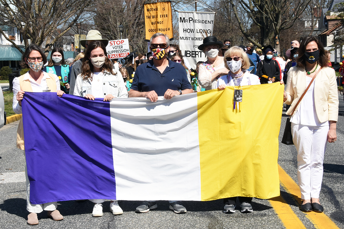 Four women and a man holding a suffrage flag