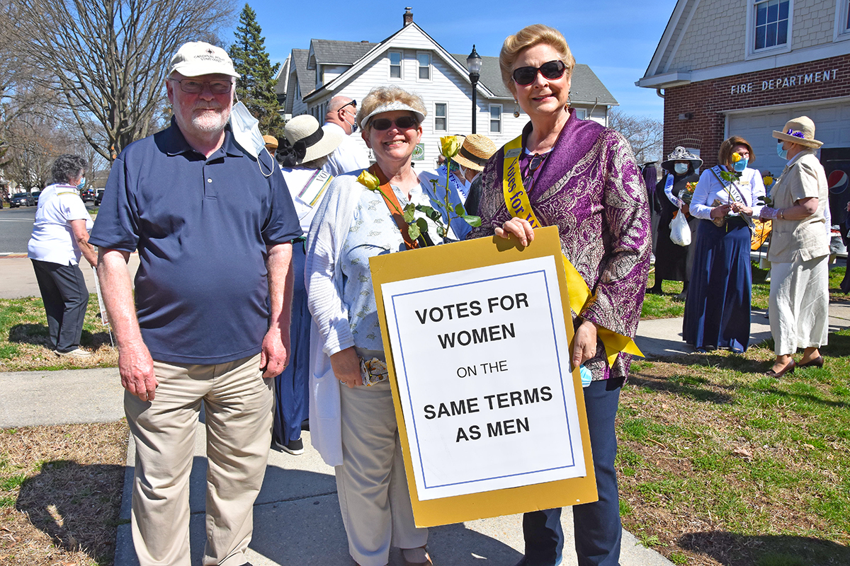 """Kit Bailey Bea Dane Kate Stevenson with a sign that says """"Votes for Women on the same terms as men."""""""