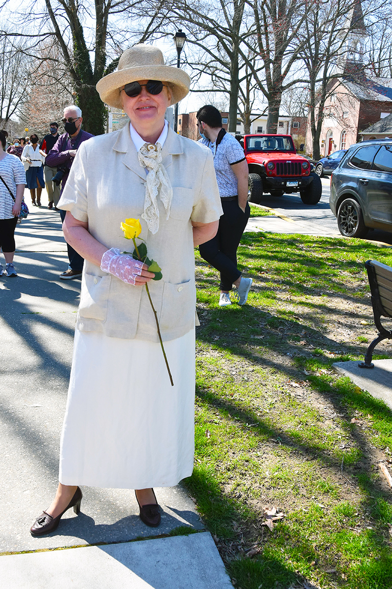 Lisa Orisich dressed in a cream colored dress suit, carrying a yellow rose