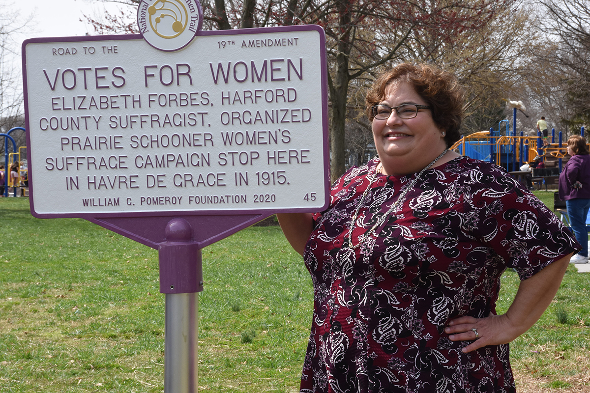 Maria Darby, MWHC Board President, stands next to marker