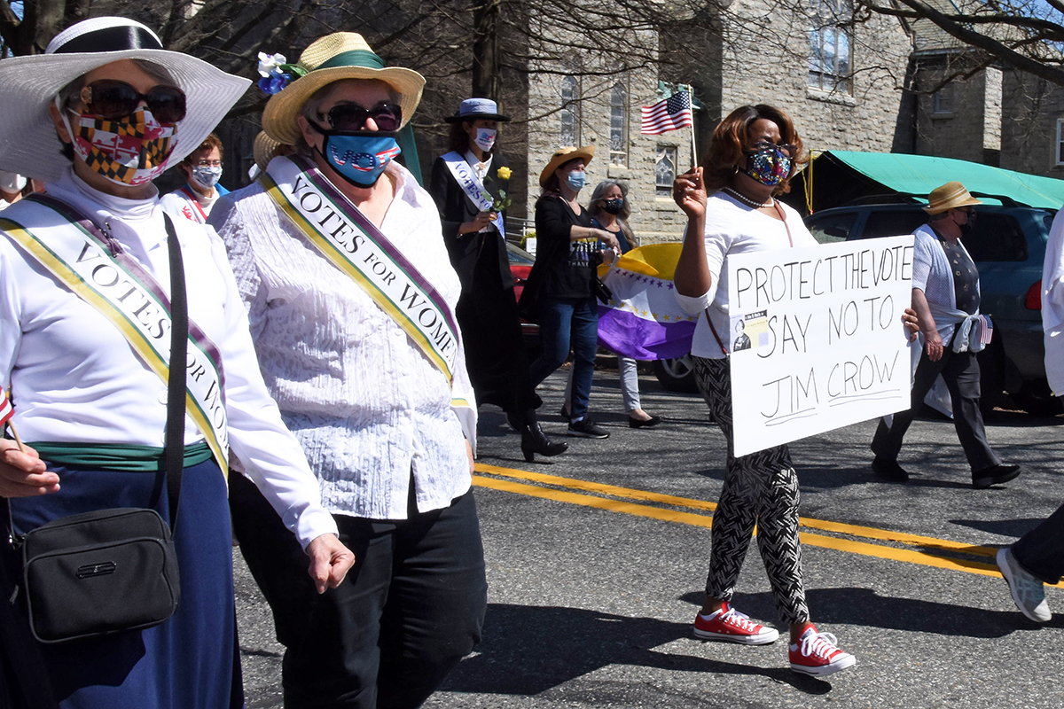 """Two women with votes for women sashes and another carrying a sign that says """"Say no to Jim Crow."""""""