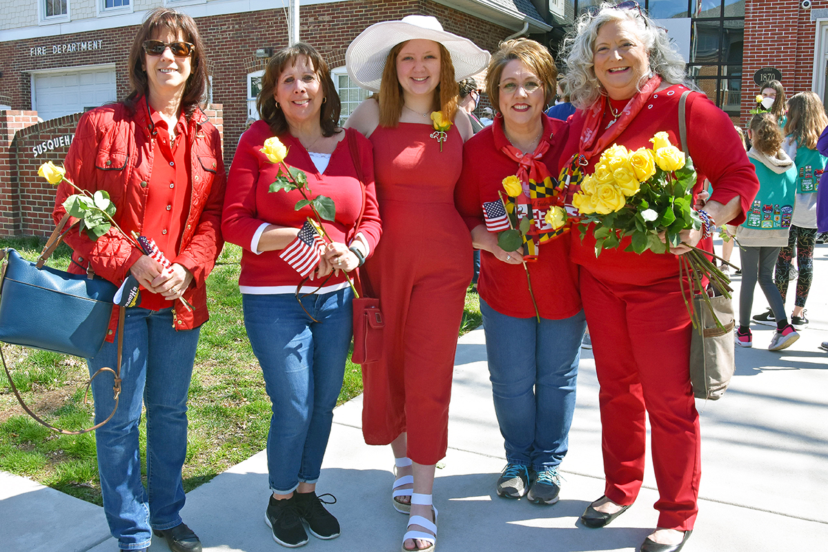 Five women from the local Republican chapter, dressed in red and carrying yellow roses